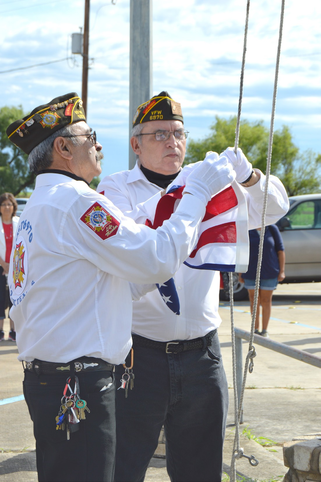 Roy Casarez (left) and Joe Vela (right) attach the American Flag to be raised and then lowered it to half staff in honor of our nation's veterans, especially those who lost their lives while defending our country. The ceremony was held at the Poteet VFW Post 6970 on Monday, May 30.