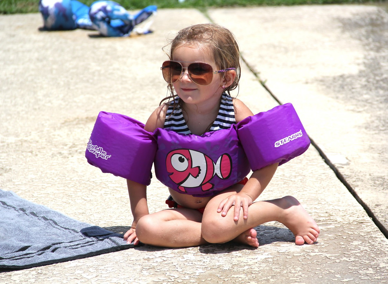 Kadi Wilson (left), eight, jumps in the Pleasanton Pool to kick off her summer while two year old Khloe Roberts (above) sports her big sunglasses while soaking up the delicious sun. The Pleasanton Pool officially opened on Tuesday, June 7 for all to enjoy.