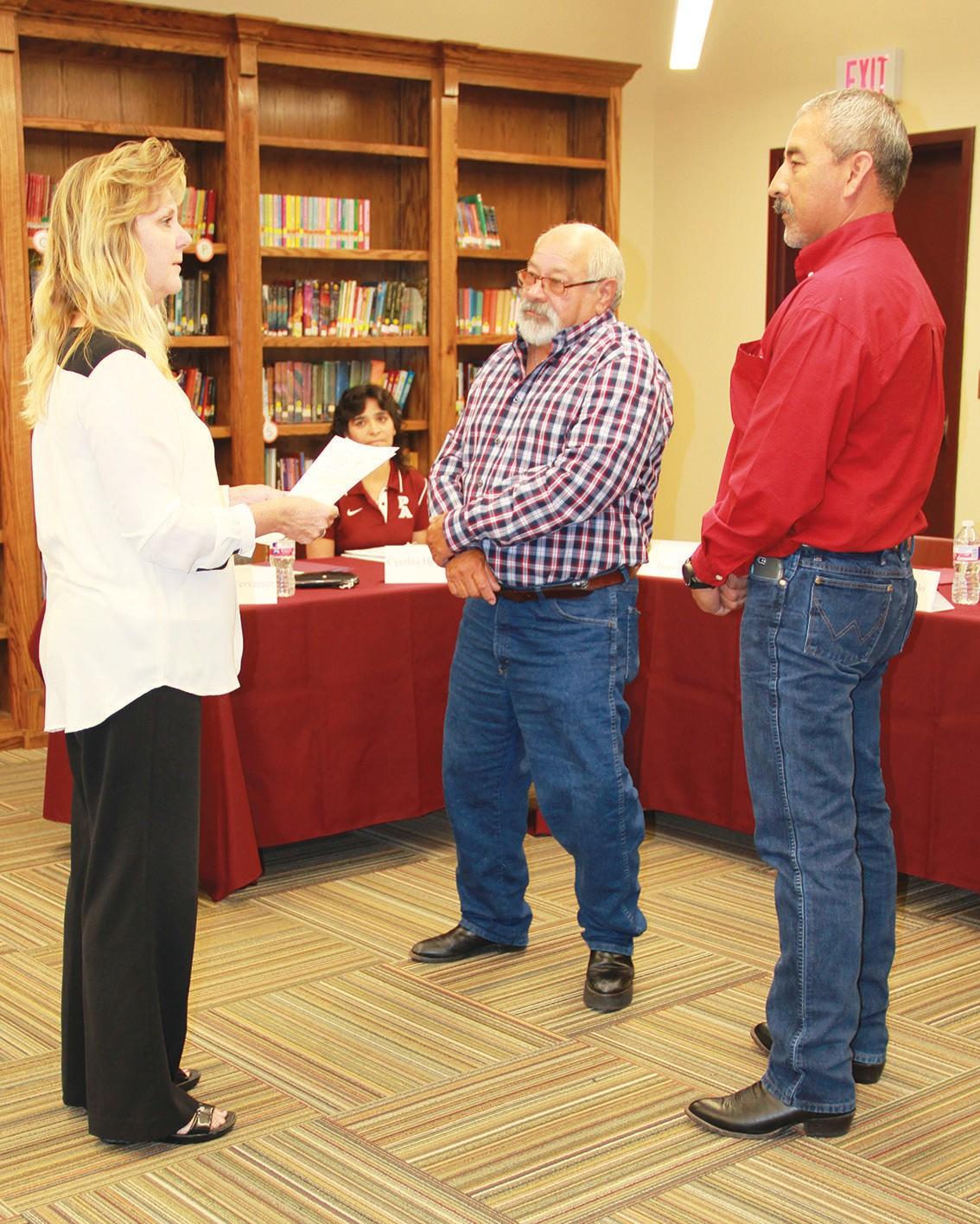 Suzanne Jenschke swears in returning school board member Louis Vasquez and new board member Diego Puente at the May 16 Poteet ISD School Board meeting.